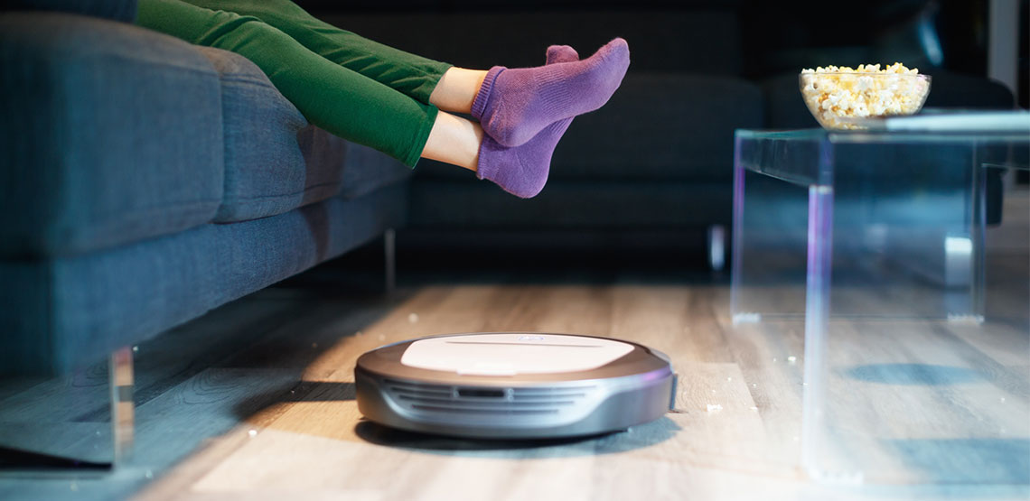Robot vacuum patrols living room while someone sits on couch