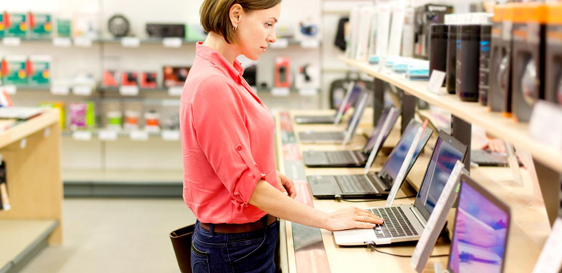 Woman in store trying out laptops