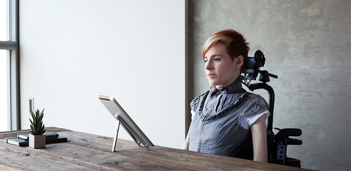 Woman in wheelchair with tablet in front on desk