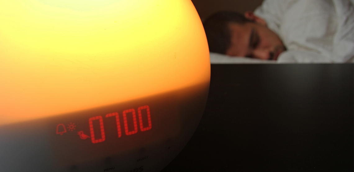 Light alarm clock with man sleeping in bed in background