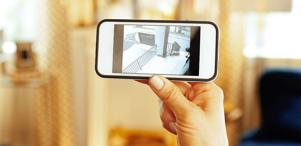 Woman looking at security camera footage on phone
